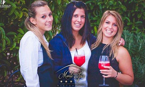 Tre donne che sorridono, due hanno un coctail di color rosso in mano