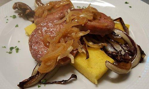 Piatto di carne con polenta, cipolle caramellate, prezzemolo