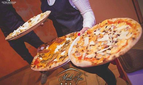 Un cameriere sta portando tre pizze