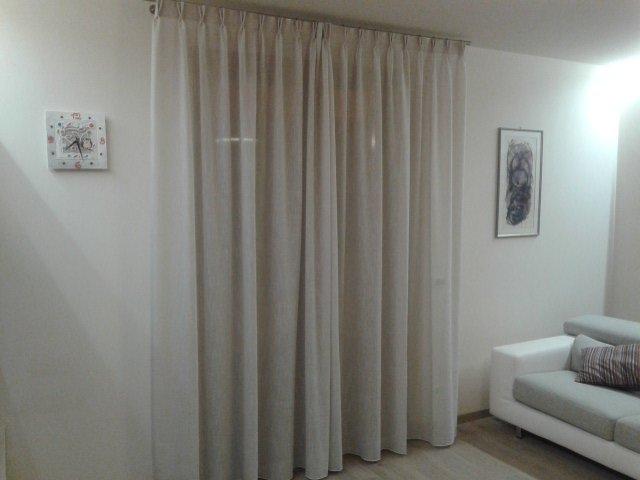 una sala con le tende a plisse di color bianco
