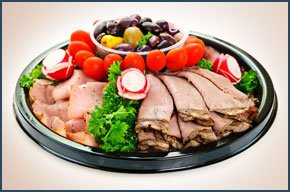 a platter of cooked meats and salad