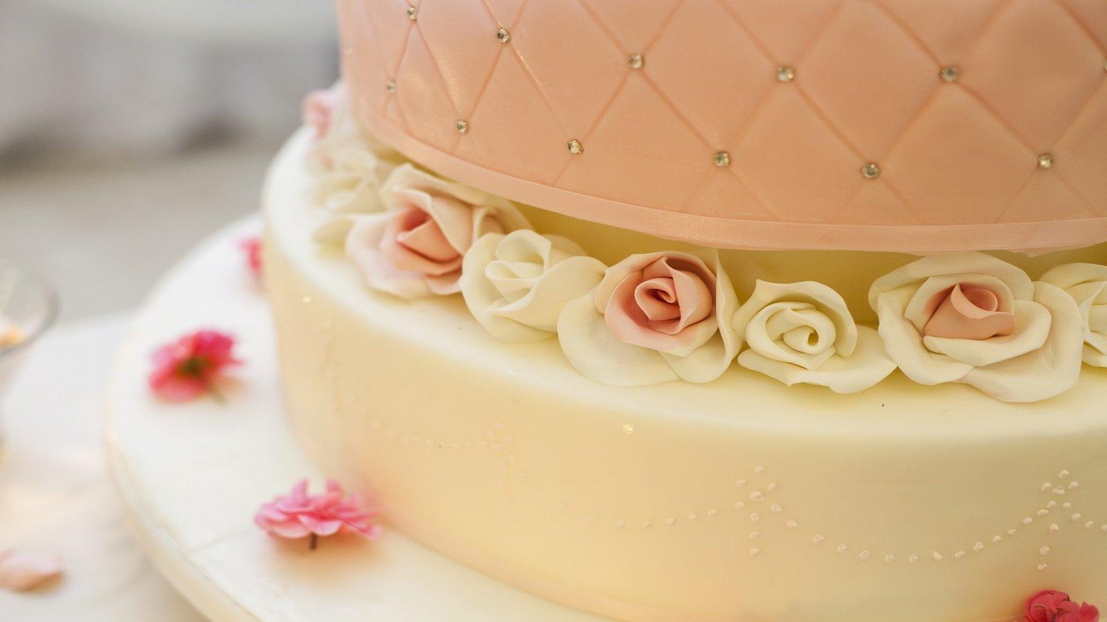 una torta a due piani con glassa bianca e rosa con delle rose