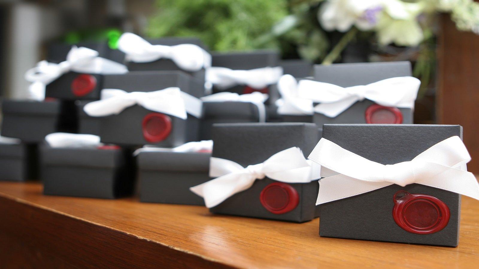 delle scatoline nere con dei fiocchi bianchi