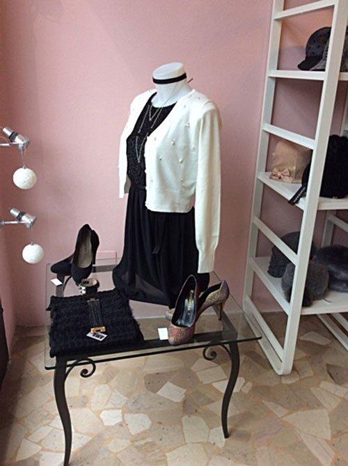 Un tavolino in cristallo con una sciarpa ,due paia di scarpe con tacchi, un manichino da donna con un abito nero e un golf bianco
