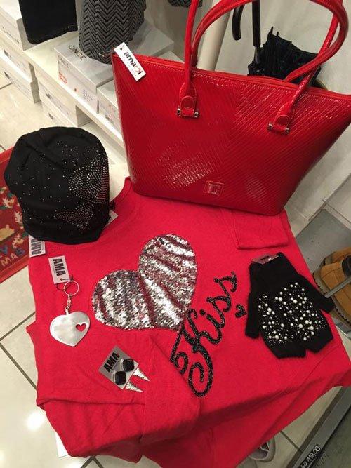 Una maglia di color fucsia con un disegno a cuore e la scritta Kiss, un cappellino di lana di color nero,una borsa di color rosso e altri accessori