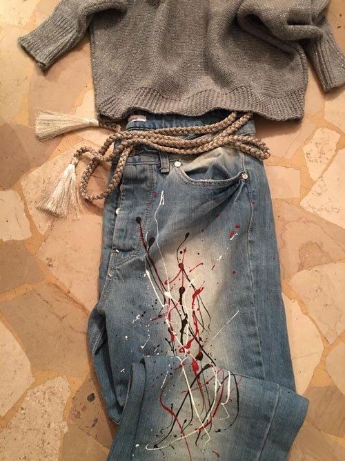 Un golf di color grigio, un paio di jeans di color blu e una cintura con un cordino e delle  frangette