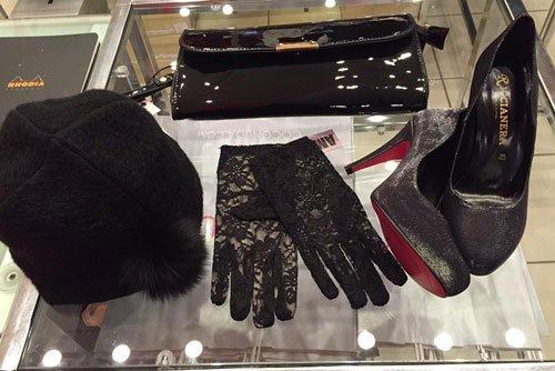 Un cappellino di lana, un paio di guanti di pizzo, un paio di scarpe coi  tacchi e un portafoglio di color nero appoggiato su un tavolino di cristallo