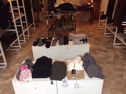 dei piccoli mobiletti bianchi con sopra dei cappellini di lana,guanti e altri vestiti all'interno di un negozio