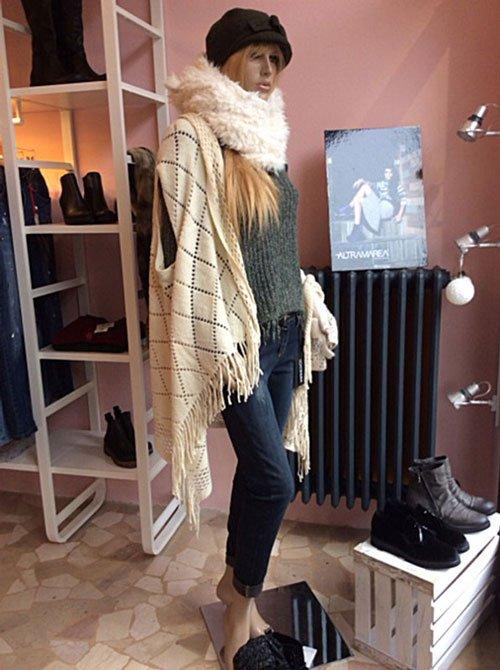 Un manichino da donna con un paio di jeans,un maglione,una mantella di color beige e degli scaffali dietro con stivaletti