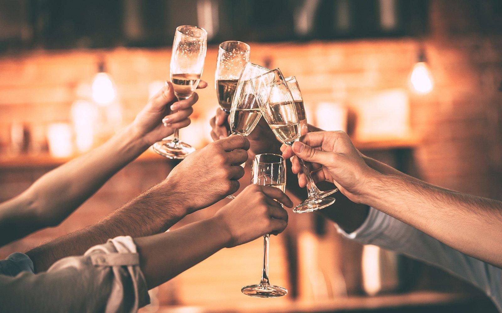 delle mani di alcune persone con dei bicchieri di vino mentre brindano