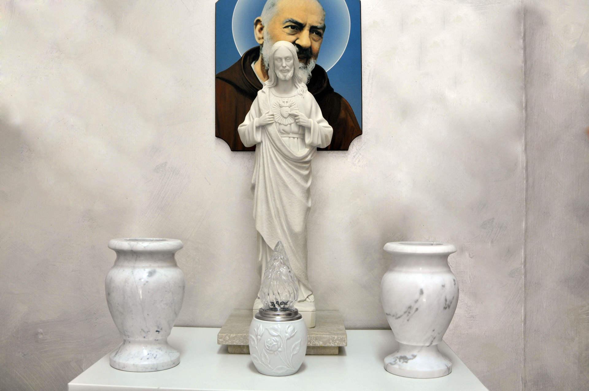 vasi votivi e statua della vergine con poster di padre pio sullo sfondo