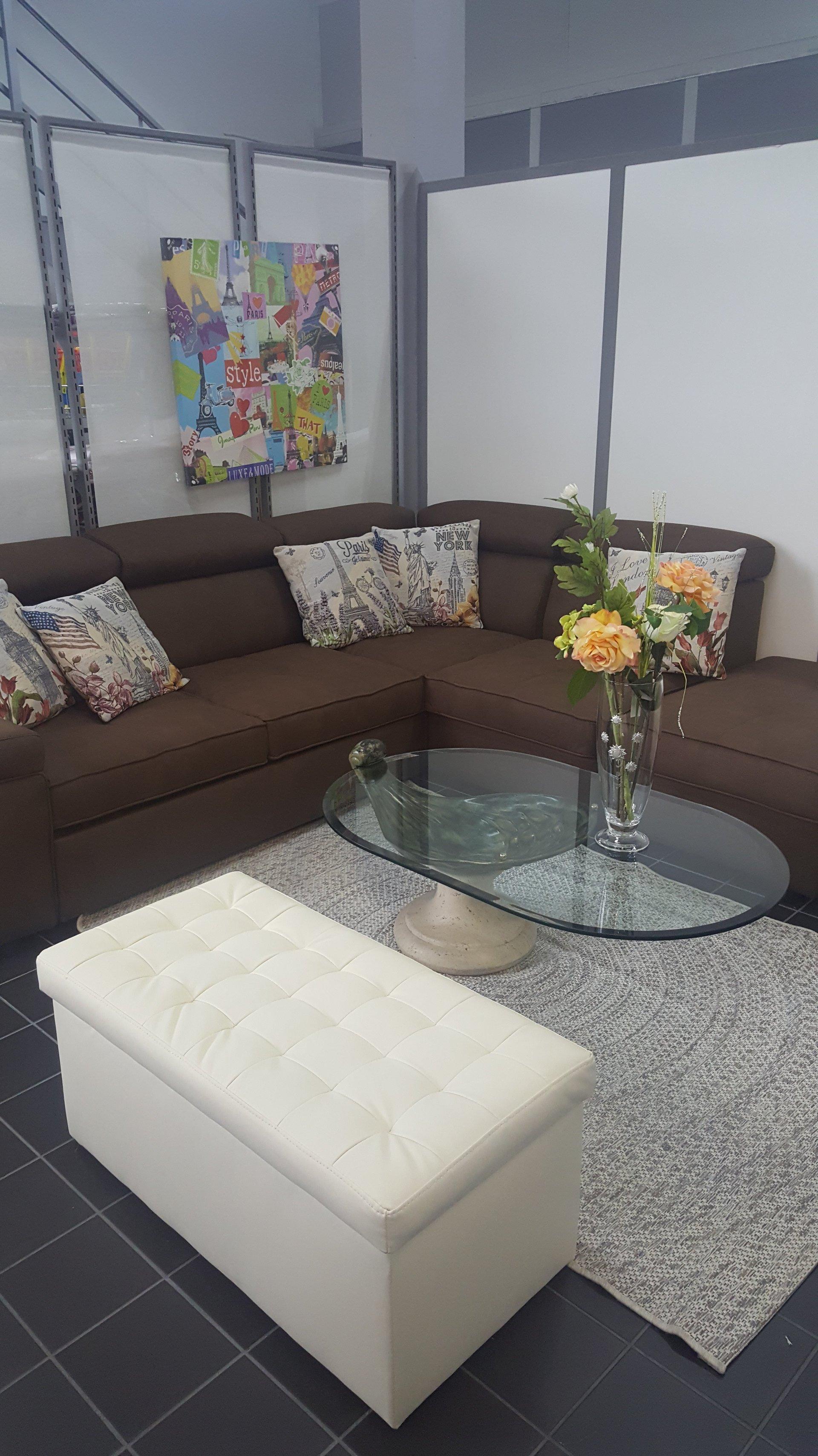divano marroncino con tavolo di vetro