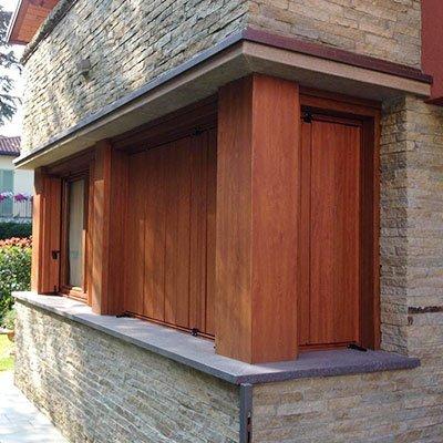 delle colonne in legno con delle persiane in una casa con mattoni grigi a vista visti dall'esterno