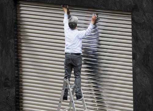un uomo di spalle e in piedi su una scala mentre sta montando una serranda in metallo