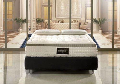 un letto di color grigio e un materasso della marca Magniflex con due cuscini