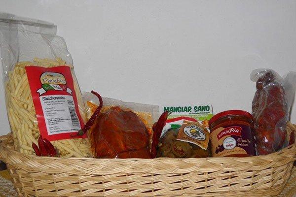 un cesto con una confezione di maccheroncini e altri prodotti in vasetto