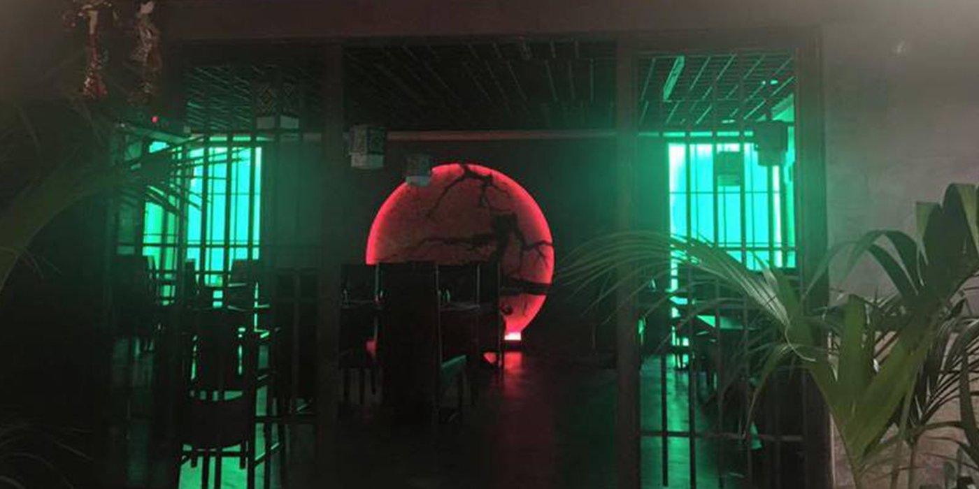 all'interno del locale due piante su entrambi i lati e una porta stile cancello marrone aperta con vista dei tavoli, in fondo un immagine della Terra di color rosso e delle luci verdi
