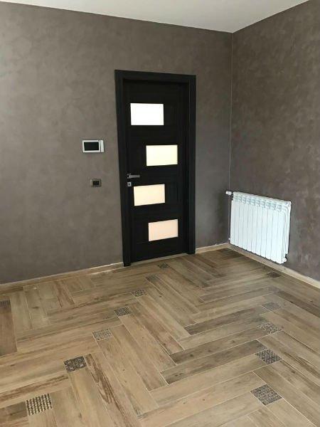 Porta di legno scuro con rectangulos di vetro e un radiatore