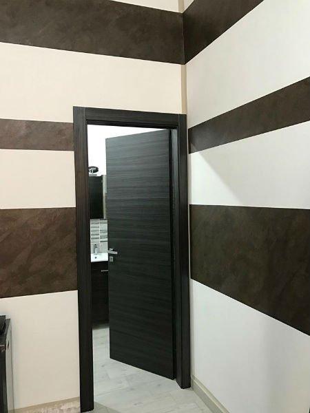 Stanza decorata a grandi tratti bianche e bruni e porta aperta