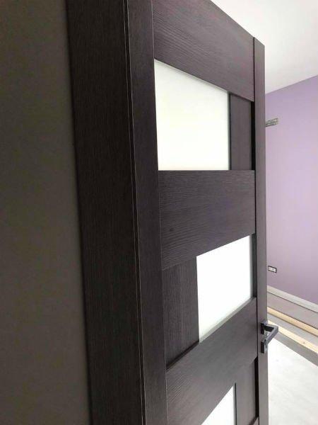 Porta di legno scuro con decorazioni di vetro