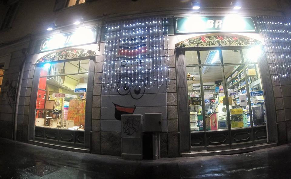 le due vetrine del colorificio viste dall'esterno illuminate e con decorazioni natalizie