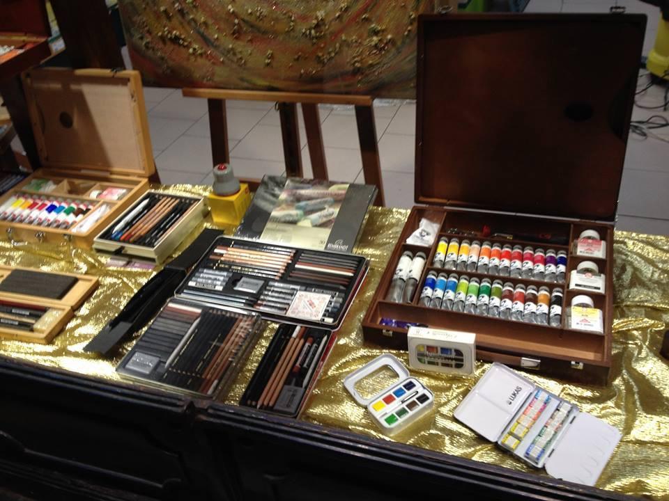 scatole con tempere,matite e pennarelli esposte su un tavolo con una tovaglia di plastica gialla brillante