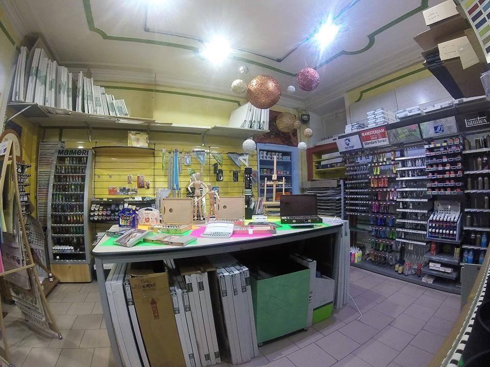 interno del negozio con un tavolo in mezzo con sopra degli oggetti e una serie di pannelli a muro con articoli in vendita esposti