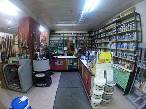 interno del colorificio con secchi di pitture esposti a terra e sugli scaffali e altri prodotti