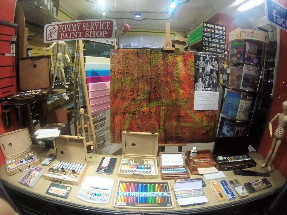 un tavolo con sopra delle scatole con matite,tempere e altri colori e di fronte un pannello pitturato di rosso e verde e un cartello rosso con scritto Tommy Service Paint Shop