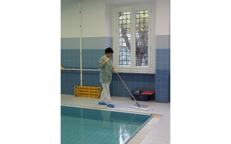 donna pulisce una piscina