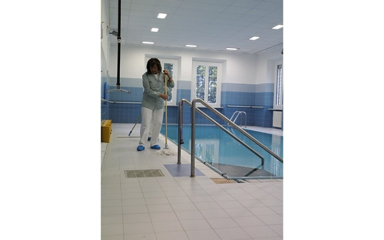 lavoratrice della cooperativa durante la pulizia di una piscina