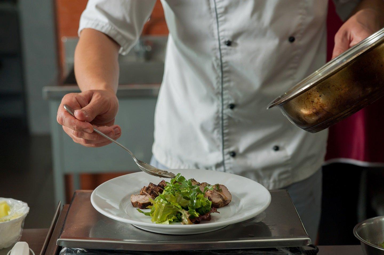 cuoco guarnisce piatto