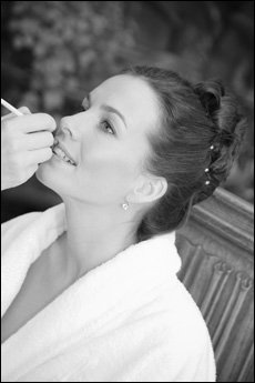 applying lipstick on bride