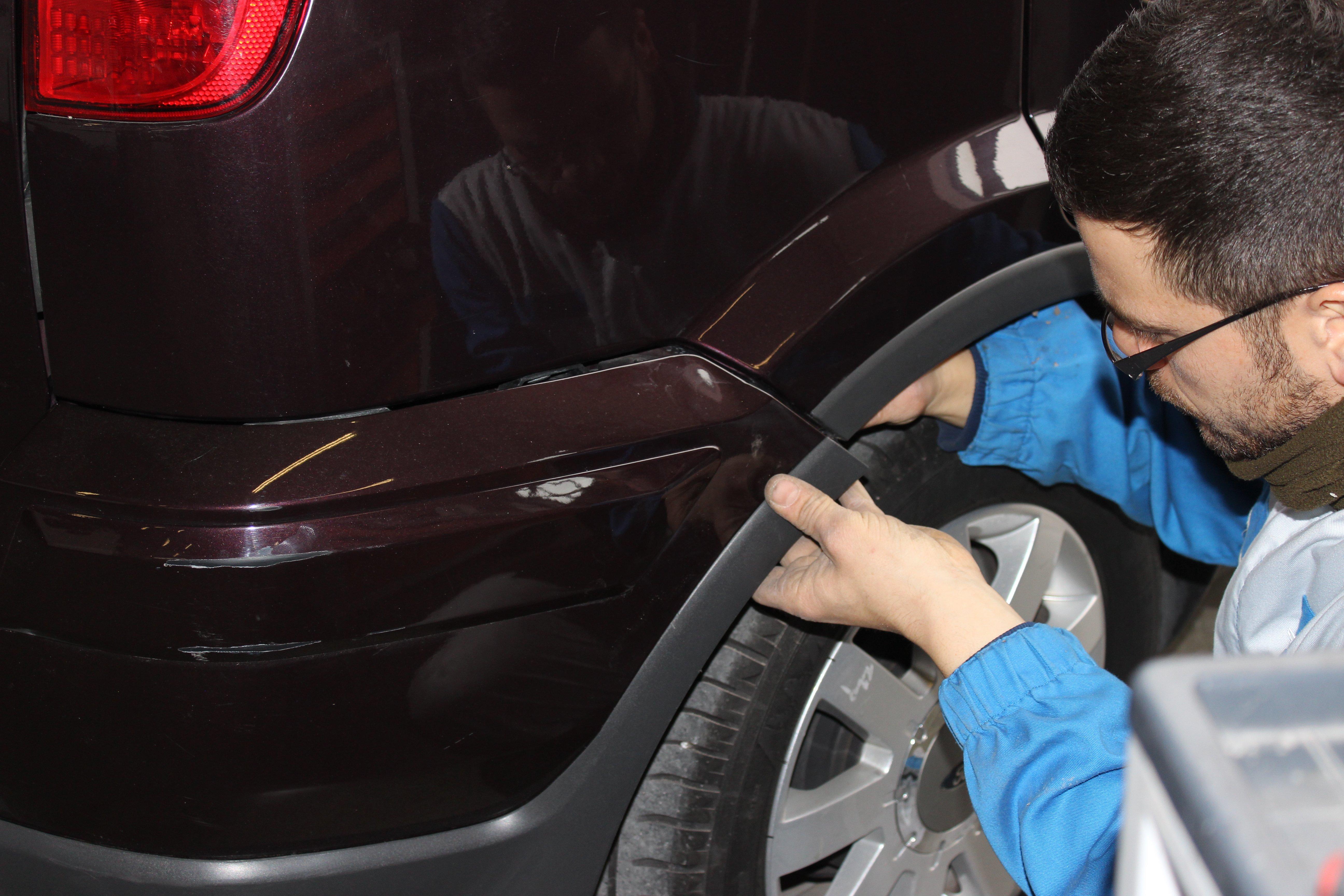 Un meccanico analizza una parte di carrozzeria di un'auto