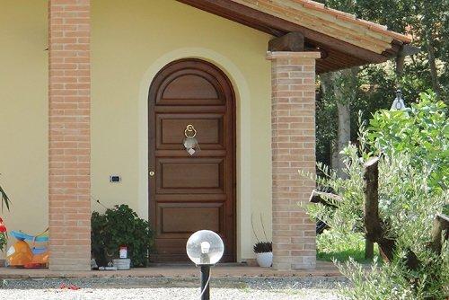 vista esterna di una casa gialla con porta in legno
