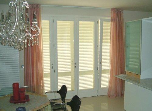 sala da pranzo con porte in vetro e tende