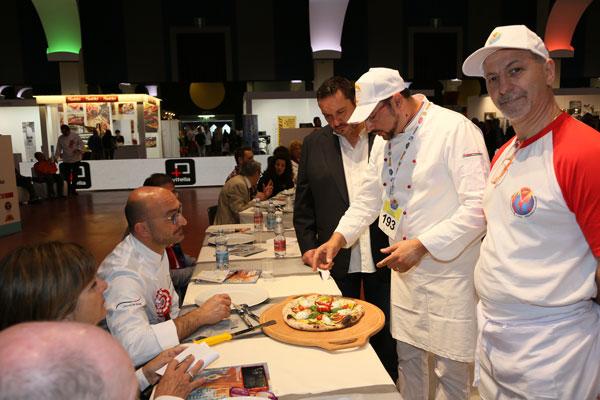 Un cuoco in piedi mentre parla con delle persone sedute al tavolo