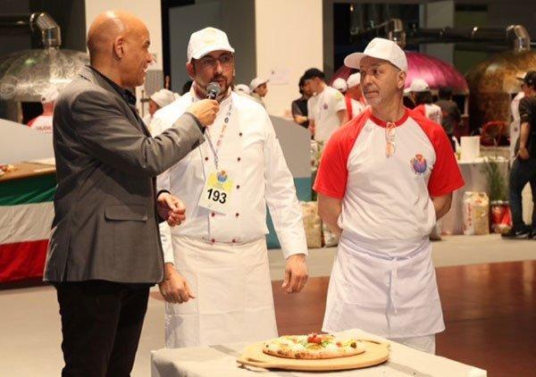 un uomo con un completo nero con un microfono in mano e due cuochi in piedi davanti un tavolino con un tagliere di pizza