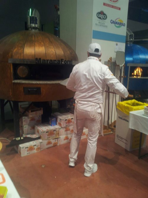Un cuoco visto dal dietro mentre inforna una pizza nel forno a legna