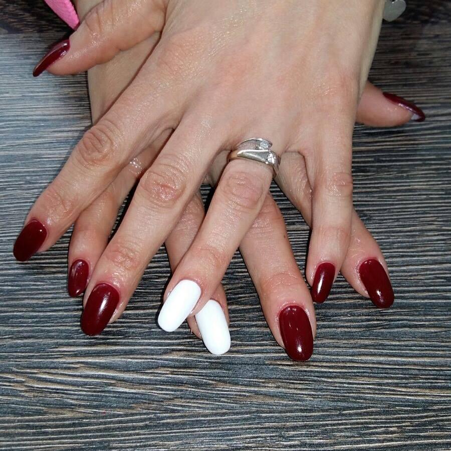 mani di una donna con smalto rosso e bianco