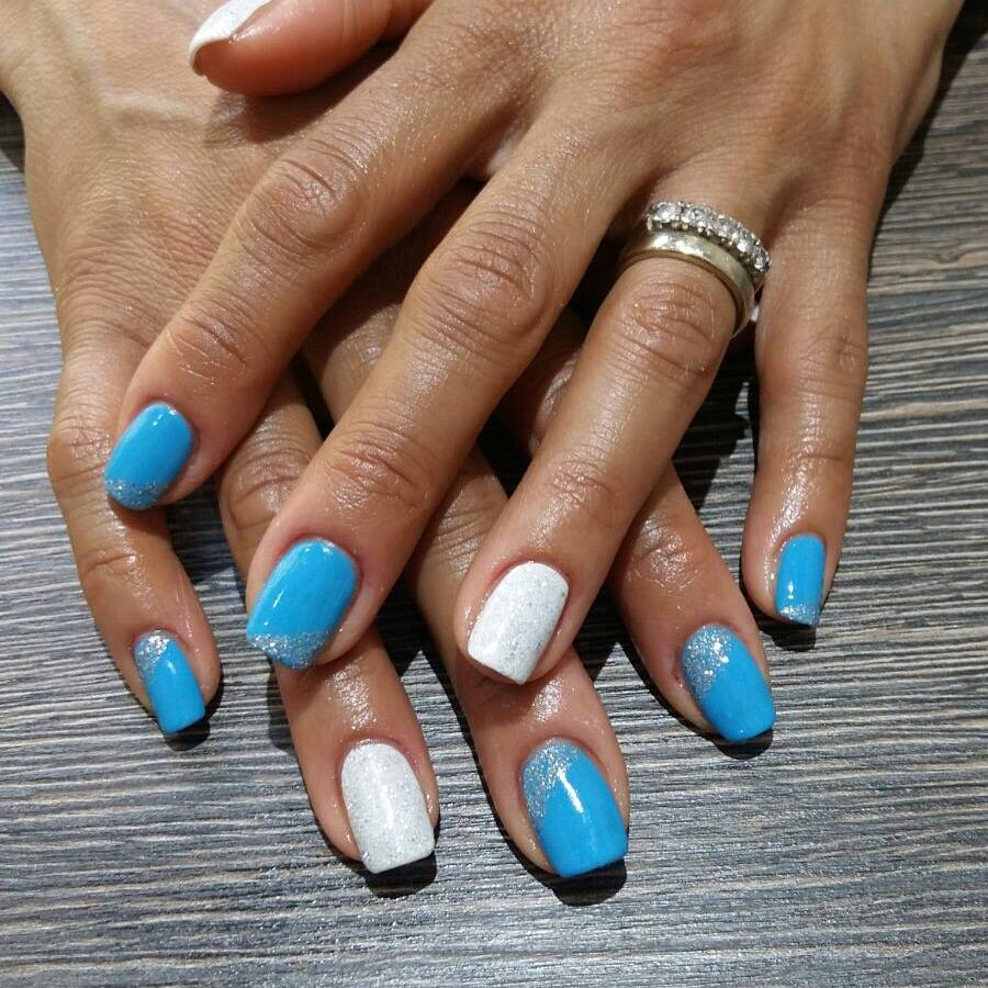 mani di donna con smalto blu e bianco