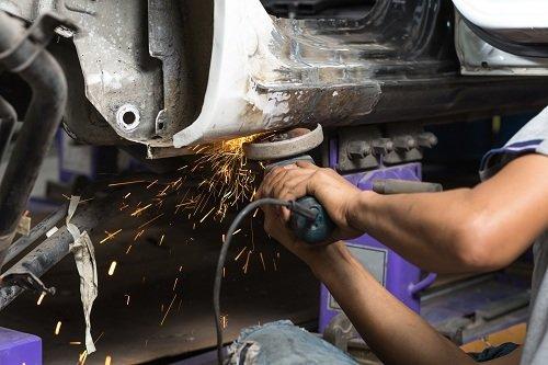 Carrozziere che lavora la lamiera della carrozzeria di un'auto