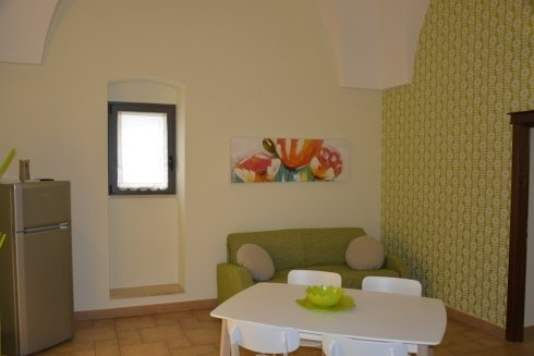 Sala da pranzo con frigorifero e divano
