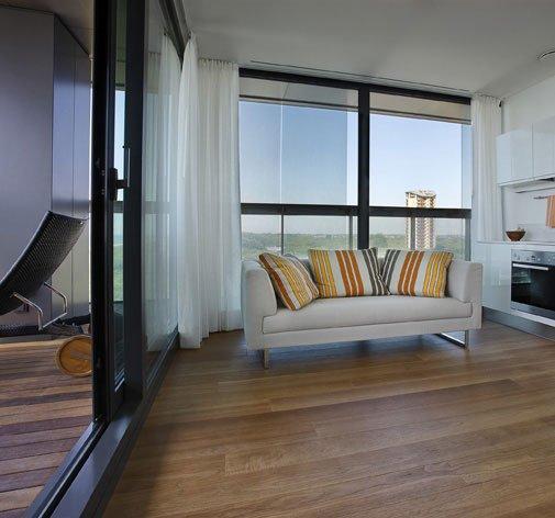 un divano bianco con dei cuscini e un pavimento in parquet