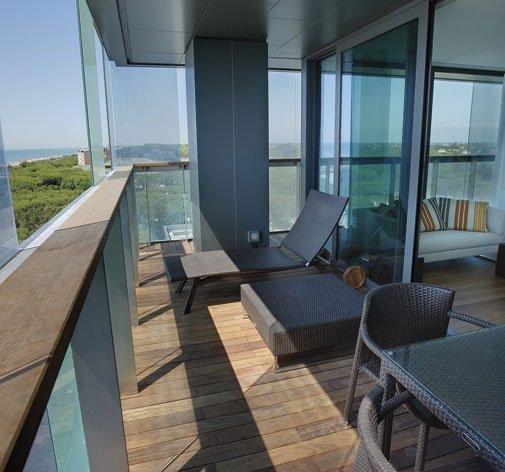 un balcone con un pavimento in parquet, uno sdraio e un tavolo con delle sedie