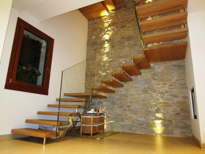 dei gradini in legno con corrimano in vetro