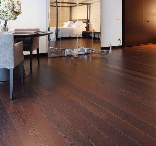 un pavimento in parquet, un tavolo con delle sedie e vista di una camera da letto
