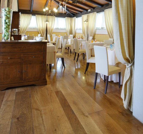 vista dei tavoli con delle sedie bianche in un ristorante con un pavimento in parquet