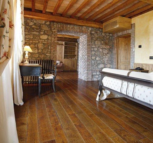 interno di una casa con muri in pietra e pavimento in parquet