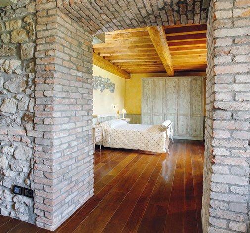 vista di una camera da letto in una casa con pareti in pietra e pavimento in parquet